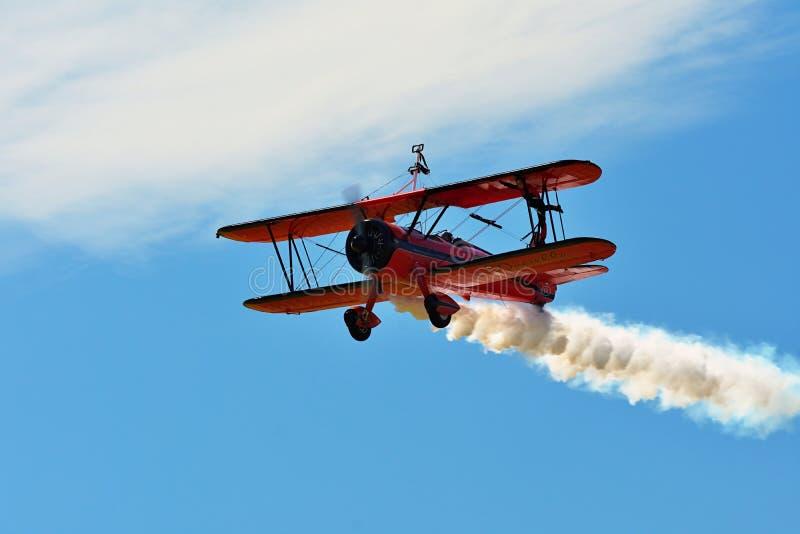 Pamiątkowy Airshow Czerwony Stearman biplanu latanie w kierunku kamery podczas gdy powłóczysty dym w wystawie zdjęcia stock