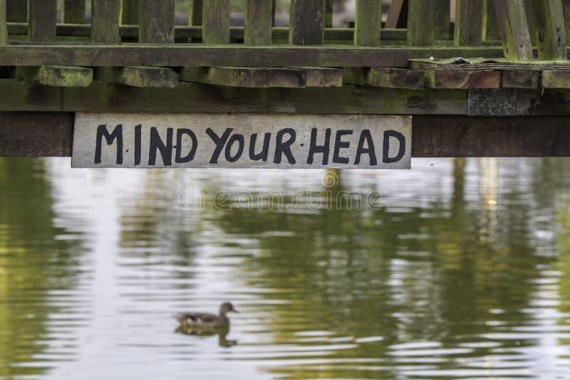 Pamięta Twój głowę - niski rzeka mosta znak zdjęcia stock