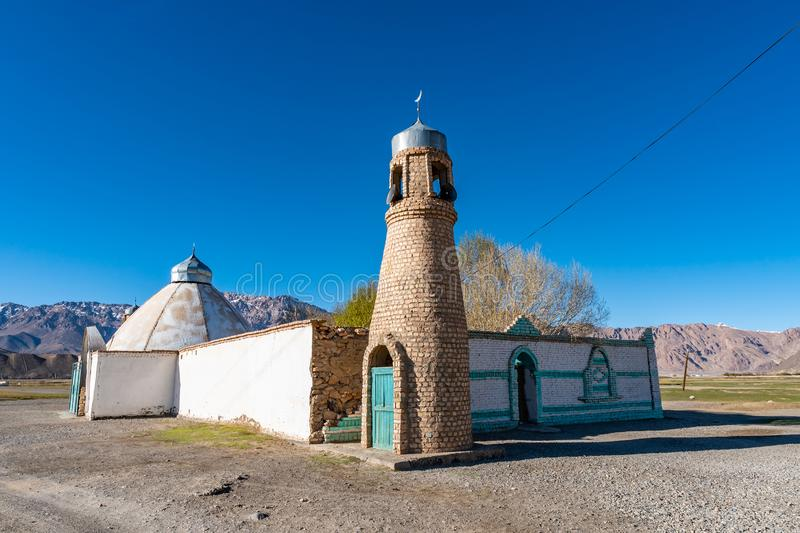 Murghab Town Mosque 16. Pamir Highway Murghab Town Mosque with Minaret Picturesque View on a Sunny Blue Sky Day royalty free stock photo