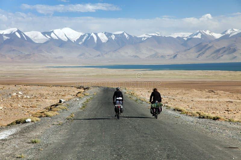 Pamir huvudväg eller Pamirskij trakt med två cyklister arkivbilder