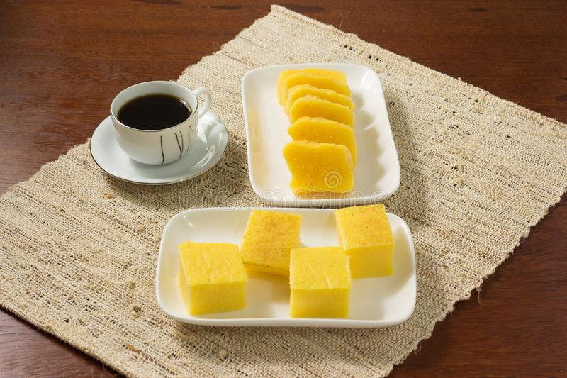 Pamonha and Canjica/Curau in a white plate with a cup of coffee in wtithe cup. on a rustic background stock images