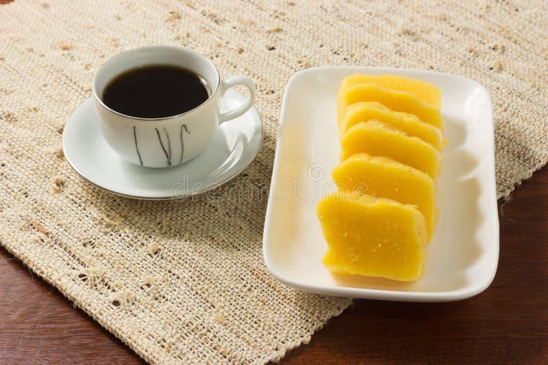 Pamonha in einer weißen Platte mit einer Schale schwarzem Kaffee auf einem rustikalen Hintergrund lizenzfreie stockfotos