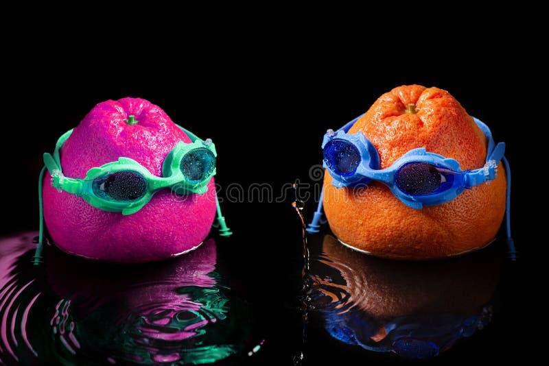 Pampelmuse zwei in schwimmenden Schutzbrillen, wie einem Mann und eine Frau, Stand im Wasser, Spritzen und Tropfen, das Konzept d stockfoto