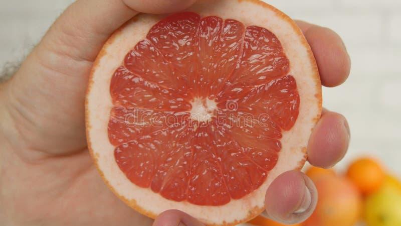Pampelmusen-Abschluss herauf Bild mit Handpressen-Hälfte der Frucht und den Saft zusammendrücken lizenzfreie stockfotografie