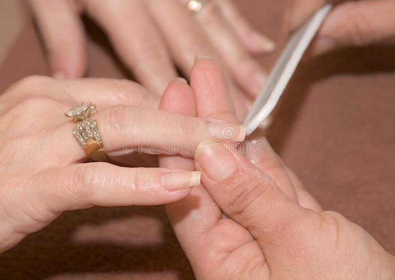 Pampered Hands Shape Up. Fingernails of pampered hands are filed into shape stock images