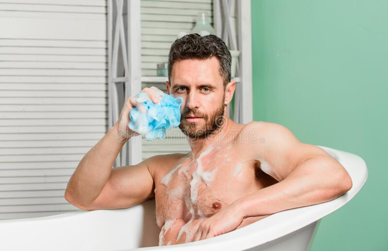 Pampering and beauty routine. Man handsome muscular guy relaxing in bathtub. Macho with sponge take bath at home stock images
