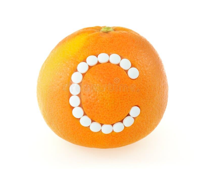Pamplemousse avec des pillules de vitamine C au-dessus du backgro blanc photographie stock