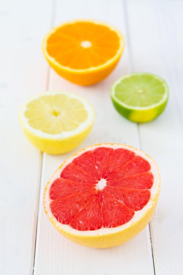 Pamplemousse, citron, chaux et orange frais de coupe sur la table en bois lumineuse image stock