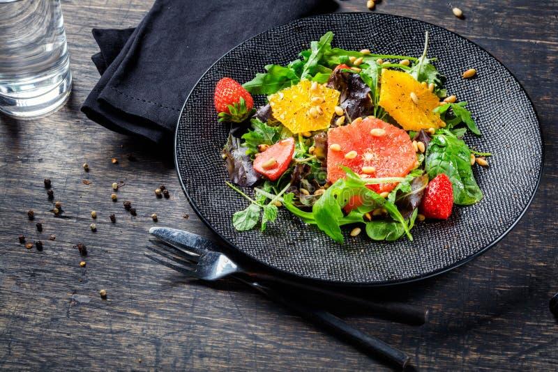 Pamplemousse et salade orange de mélange avec des pignons du plat noir photographie stock