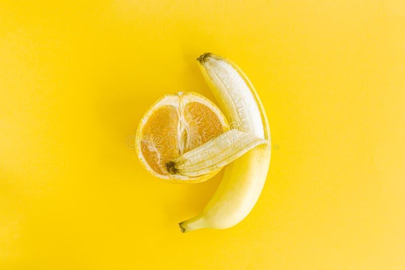 Pamplemousse rougeoyant jaune d'étreintes de banane, un concept créatif de l'amour interracial, tendresse, chaleur, bonheur et vi photos libres de droits