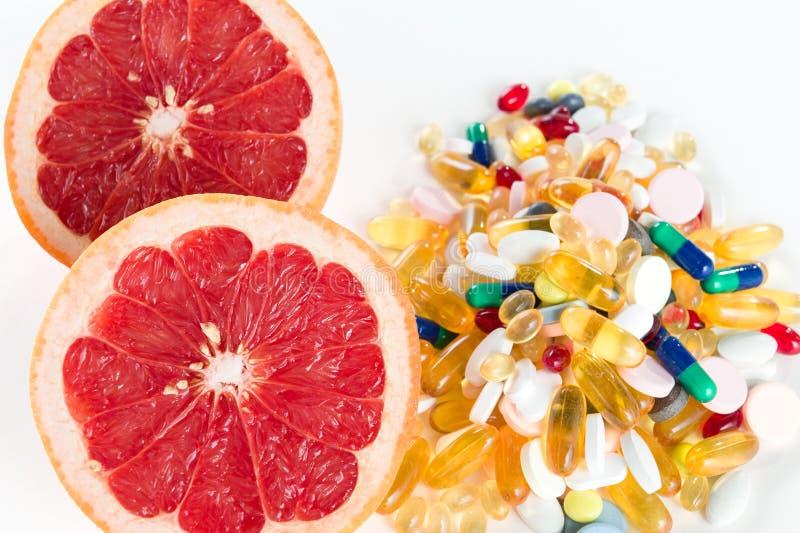 Pamplemousses et pilules, suppléments de vitamine sur le fond blanc, concept d'alimentation saine image libre de droits