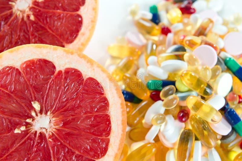 Pamplemousses roses et pilules, suppléments de vitamine sur le fond blanc, concept d'alimentation saine photo stock