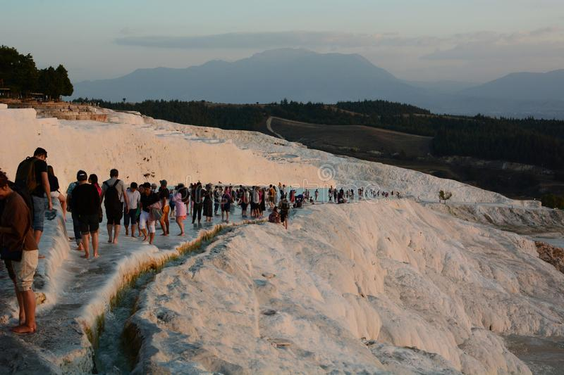 Crowd of visitors in Pamukkale. Denizli province. Turkey. Pamukkale, meaning cotton castle in Turkish, is a natural site in Denizli in southwestern Turkey; the stock images