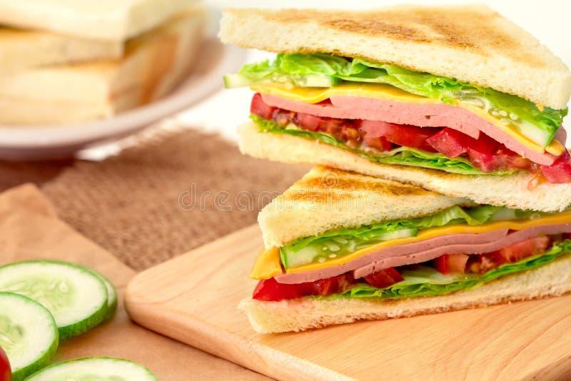 Pan asado a la parrilla cortado de los bocadillos con tocino, el jamón y el queso con imágenes de archivo libres de regalías