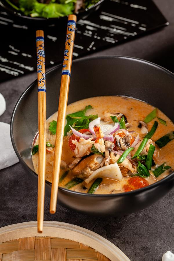 Pan-Asian cuisine concept. Japanese miso soup Tom Yam Kung with seafood, shrimps, mussels, calamari. Serving dishes. In the restaurant in the bowl. Background royalty free stock photo