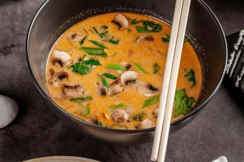 Pan-Asian cuisine concept. Japanese miso soup Tom Yam Kung with seafood, shrimps, mussels, calamari. Serving dishes. In the restaurant in the bowl. Background stock photography