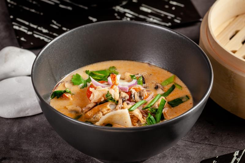 Pan-Asian cuisine concept. Japanese miso soup Tom Yam Kung with seafood, shrimps, mussels, calamari. Serving dishes. In the restaurant in the bowl. Background royalty free stock photos