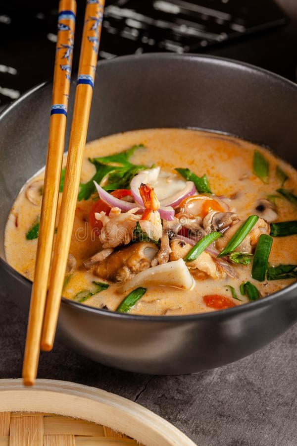 Pan-Asian cuisine concept. Japanese miso soup Tom Yam Kung with seafood, shrimps, mussels, calamari. Serving dishes. In the restaurant in the bowl. Background stock photo