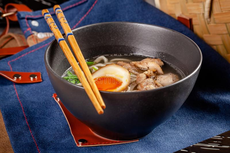 Pan-Asian cuisine concept. Japanese Ramen Soup with Chinese Noodles, Egg, Chicken and Green Onions. Serving dishes. In the restaurant in the bowl. Background royalty free stock photography