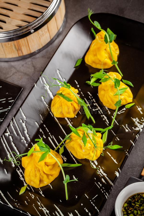 Pan-Asian cuisine concept. Wontons of yellow dough, minced meat. Japanese dumplings with minced meat. Serving dishes. In the restaurant on a black plate stock photos