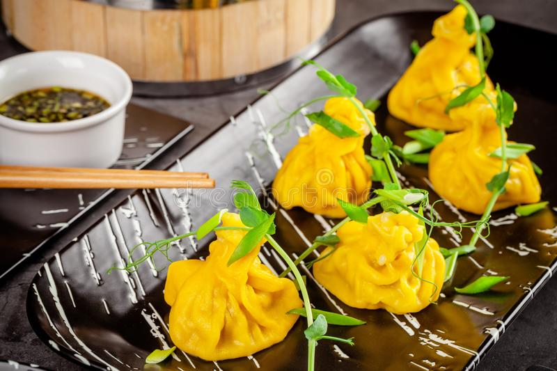 Pan-Asian cuisine concept. Wontons of yellow dough, minced meat. Japanese dumplings with minced meat. Serving dishes. In the restaurant on a black plate stock photo