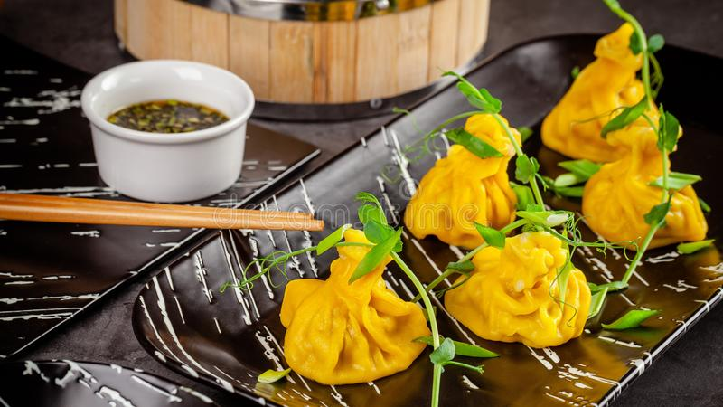 Pan-Asian cuisine concept. Wontons of yellow dough, minced meat. Japanese dumplings with minced meat. Serving dishes. In the restaurant on a black plate royalty free stock photo