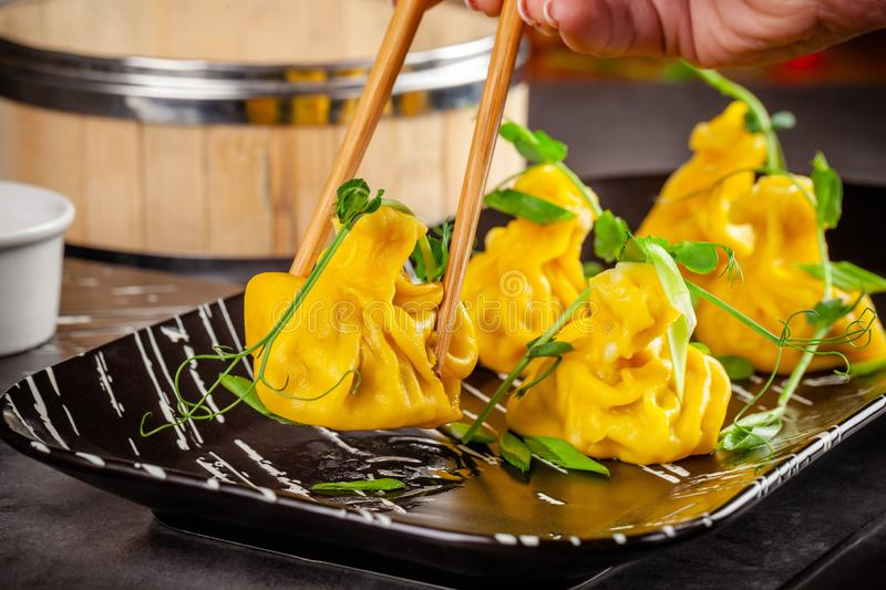 Pan-Asian cuisine concept. Wontons of yellow dough, minced meat. Japanese dumplings with minced meat. Serving dishes. In the restaurant on a black plate royalty free stock image