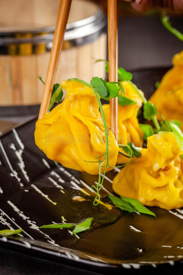 Pan-Asian cuisine concept. Wontons of yellow dough, minced meat. Japanese dumplings with minced meat. Serving dishes. In the restaurant on a black plate royalty free stock photography