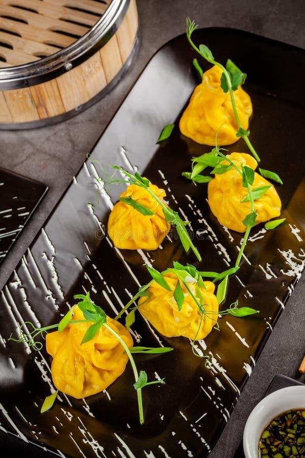 Pan-asiatisches Küchekonzept Wontons des gelben Teigs, Hackfleisch Japanische Mehlklöße mit Hackfleisch Servierteller stockfotos