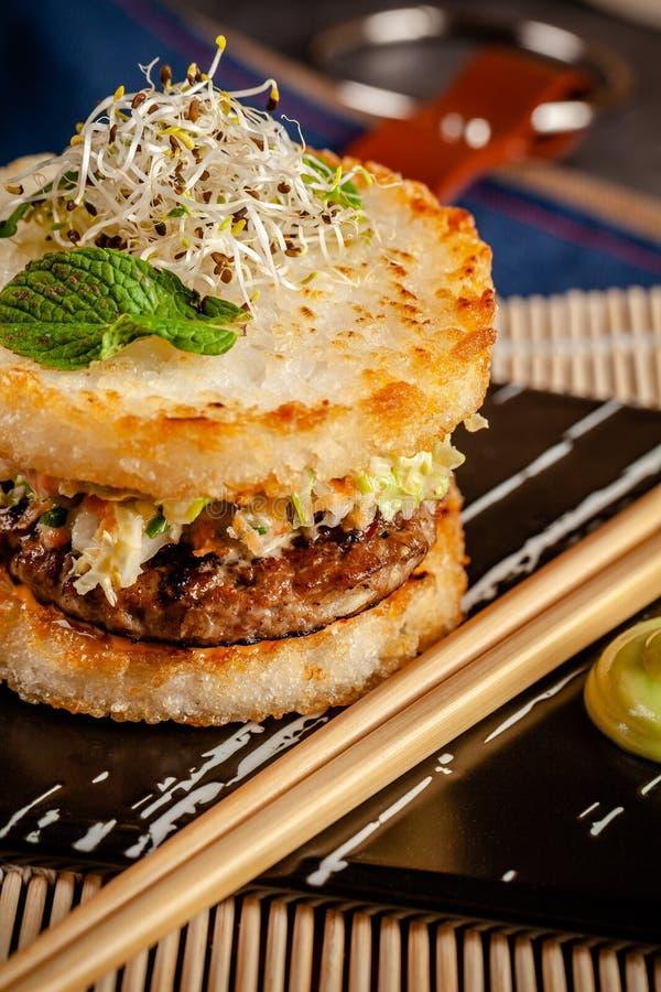 Pan-Aziatisch keukenconcept De Japanse sushihamburger maakte van van het van de rijstbrood, kip en varkensvlees vleespasteitjes,  stock foto's