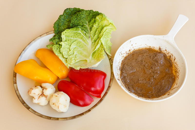 Pan of bagna cauda with a dish of vegetables as trimming. Pan of bagna cauda with a plate of red and yellow peppers ,green cabbage and topinambour serving as stock photo
