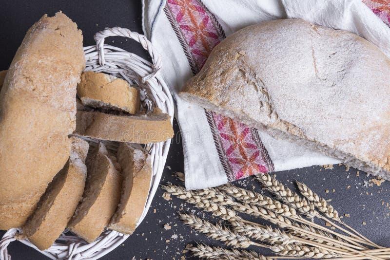 Pan cocido fresco en la tabla con los oídos del trigo Pan y bollos recientemente cocidos en panadería en fondo negro Pan rebanado imagen de archivo libre de regalías