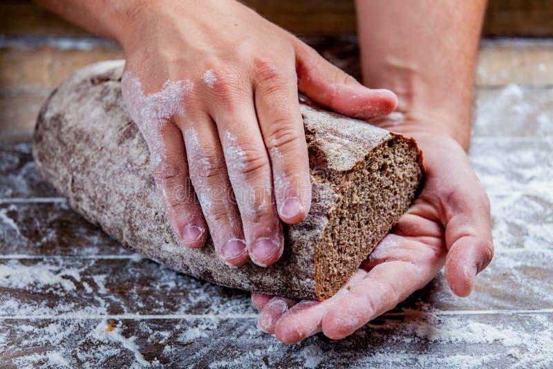 Pan cocido libre del gluten en manos del panadero fotos de archivo libres de regalías