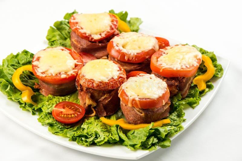 Pan con carne delicioso con espinaca, queso y el tomate en la placa en el fondo blanco fotos de archivo libres de regalías