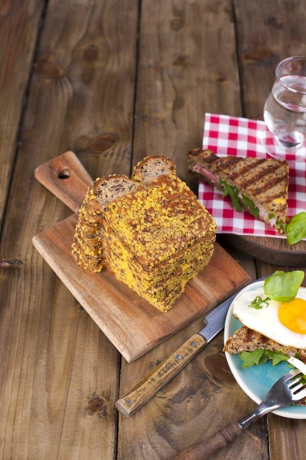 Pan con los cereales de desayuno, bocadillo y huevo, en un fondo del árbol Copie el espacio imagen de archivo
