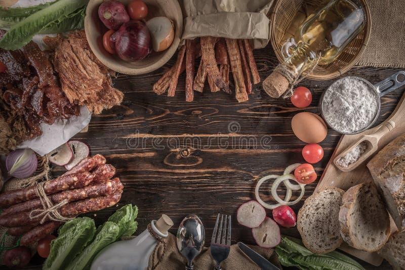 Pan con los pedazos deliciosos del jamón, de la salchicha, de los tomates, de la ensalada y de la verdura cortados - disco de la  imagenes de archivo