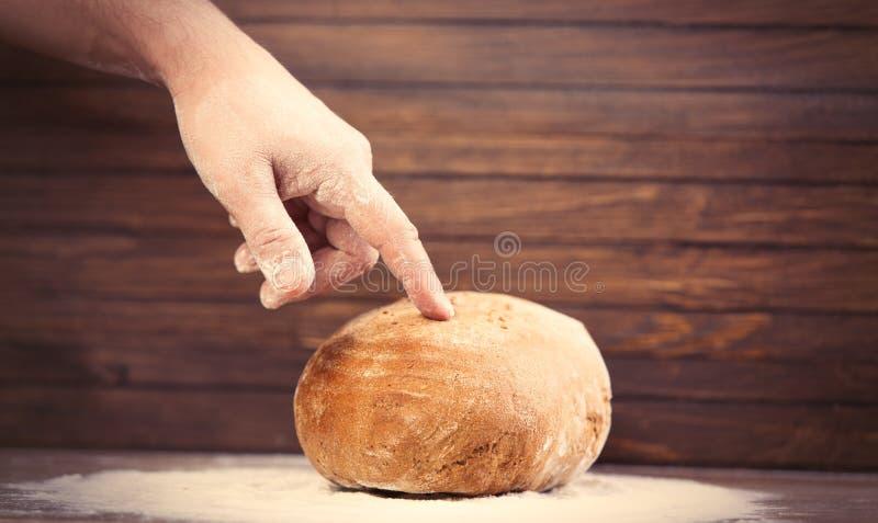 Pan conmovedor del pan de la mano masculina en la parte posterior de madera marrón maravillosa imagen de archivo