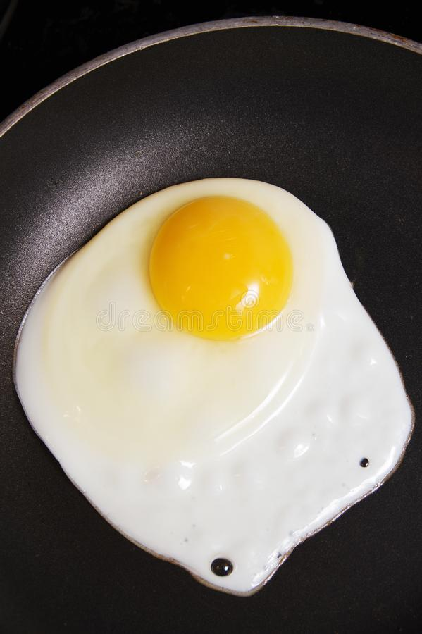 Cooking an egg in pan. A pan cooking one single egg stock photos