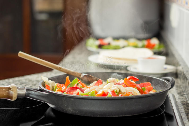 Pan cooking vegetables and chicken in the kitchen royalty free stock photography