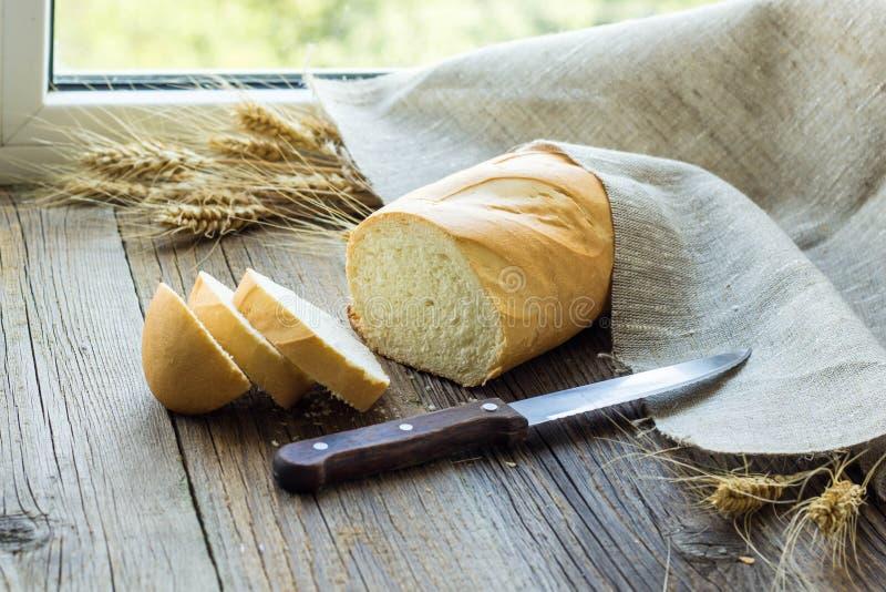 Pan cortado con los puntos del trigo en el primer de madera de la tabla fotos de archivo libres de regalías