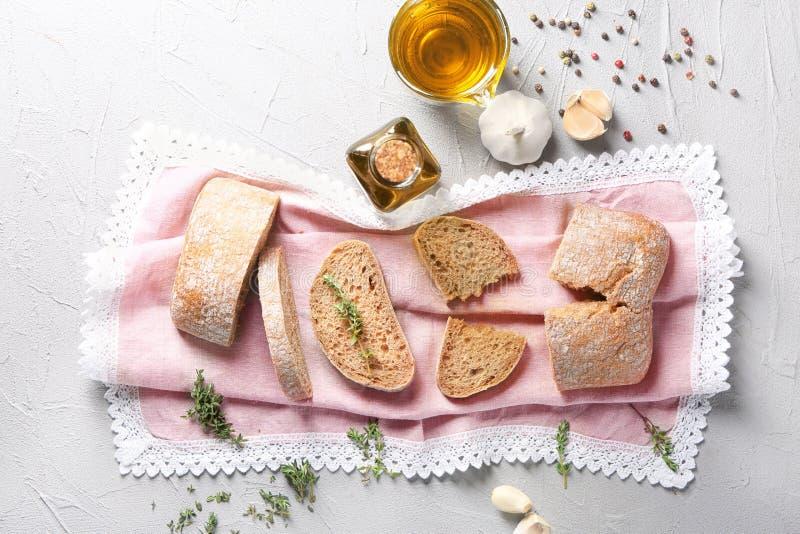Pan cortado, cristalería con aceite de oliva y ajo en la tabla, visión superior imagen de archivo