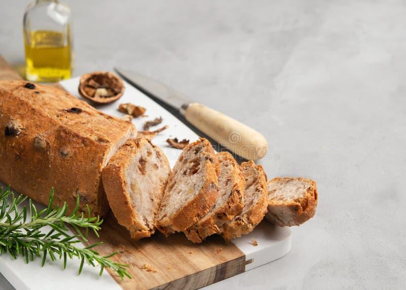 Pan cortado recientemente sano con las nueces y las pasas en tabla de cortar en fondo de piedra gris fotos de archivo