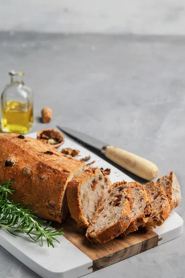 Pan cortado recientemente sano con las nueces y las pasas en tabla de cortar en fondo de piedra gris foto de archivo libre de regalías