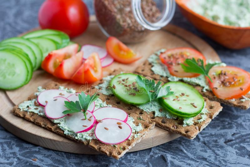 Pan de centeno curruscante con reques?n con las hierbas y las verduras estacionales asperjadas con las semillas de lino, bocadill imagen de archivo