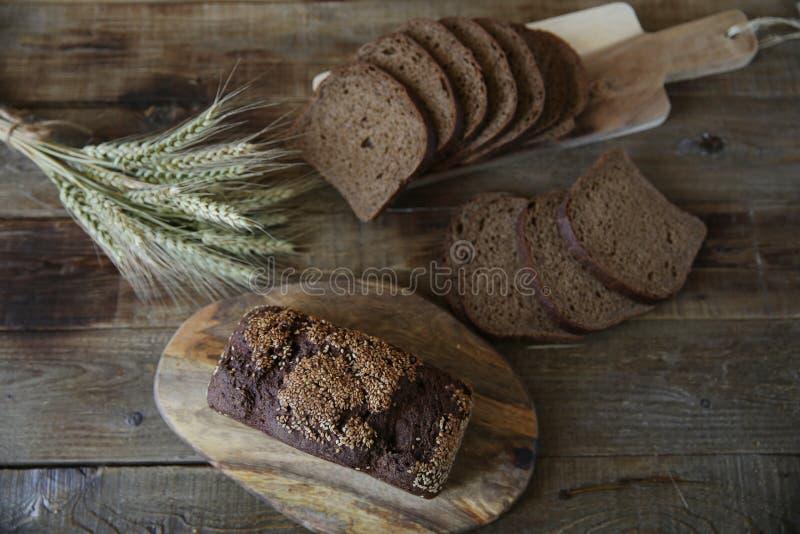 Pan de centeno entero y cortado con las semillas de sésamo y los oídos del centeno en un fondo rústico de madera Endecha plana Vi foto de archivo