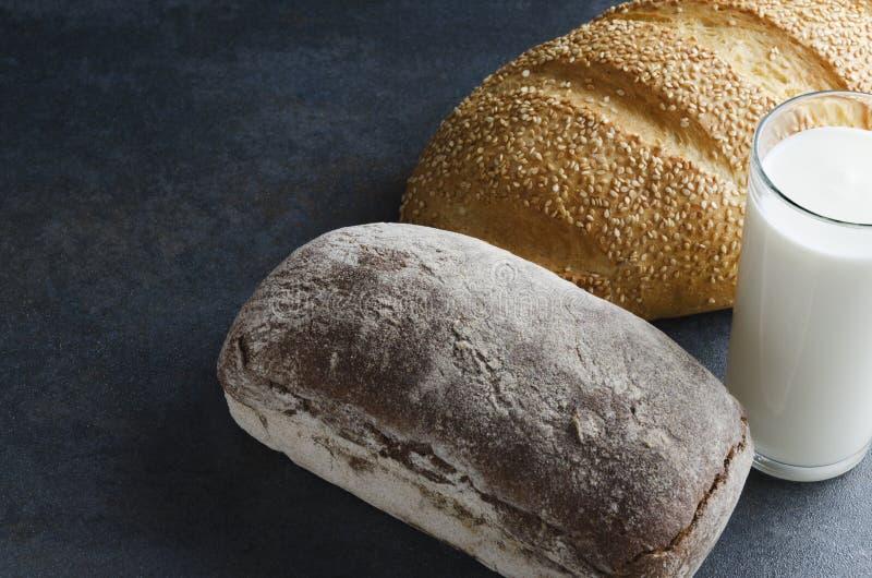 Pan de centeno fresco y pan blanco con las semillas, vidrio de leche Concepto de desayuno del país por la mañana fotografía de archivo libre de regalías