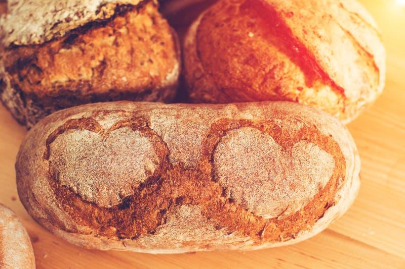 Pan de centeno rústico hecho en casa con el modelo de los corazones en una luz de madera foto de archivo libre de regalías