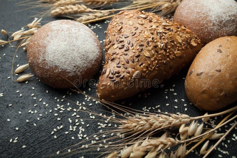 Pan de diferentes tipos en un tablero oscuro con las espiguillas del trigo, del centeno y de la avena Carbohidratos y dieta imagen de archivo