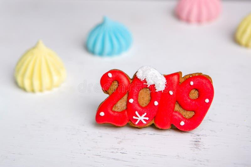 Pan de jengibre bajo la forma de números 2019 y merengue en un fondo blanco del vintage Dulces del día de fiesta Tema del Año Nue imágenes de archivo libres de regalías