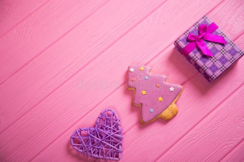 Pan de jengibre esmaltado en la forma de árbol de navidad, de corazón travieso púrpura y de caja de regalo en la tabla de madera  imágenes de archivo libres de regalías